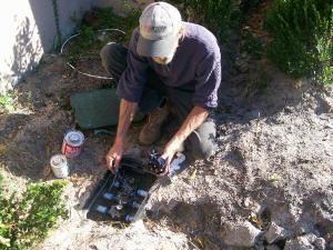a Kenmore sprinkler repair tech is doing a maintenance check on a valve box